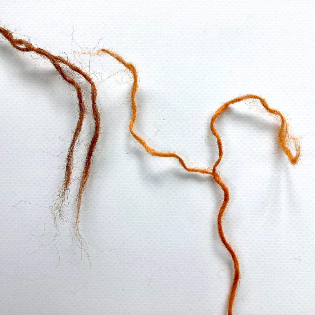 2 yarn ends (1 brown, 1 orange), with the ends teased apart in the 2 plies.