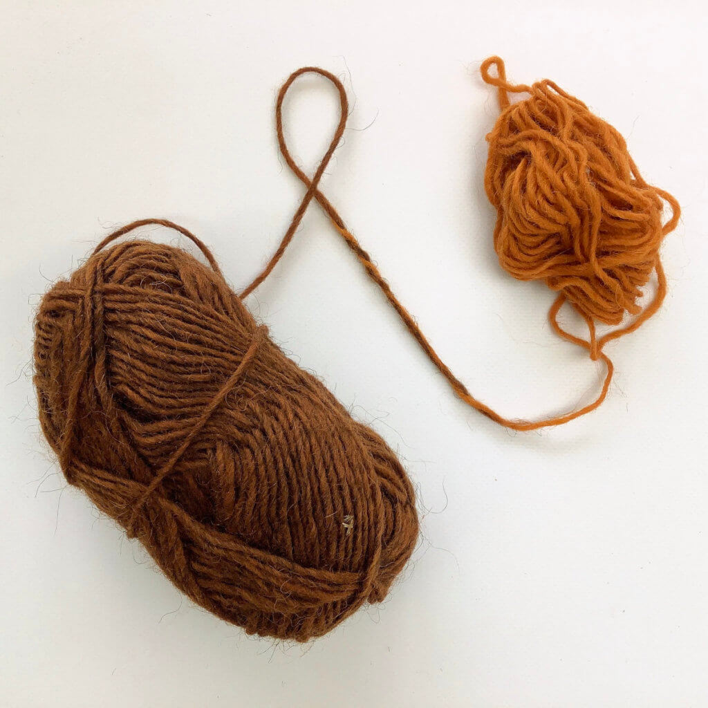 2 balls of yarn (1 orange, 1 brown) joined together on a white background.